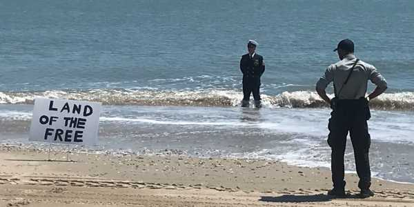 Protester wearing Navy uniform refuses to leave the ocean amid beach closures