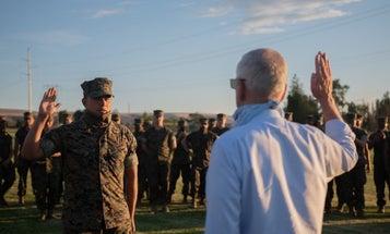 Former Defense Secretary Jim Mattis raises his knife hand to reenlist a lucky Marine corporal