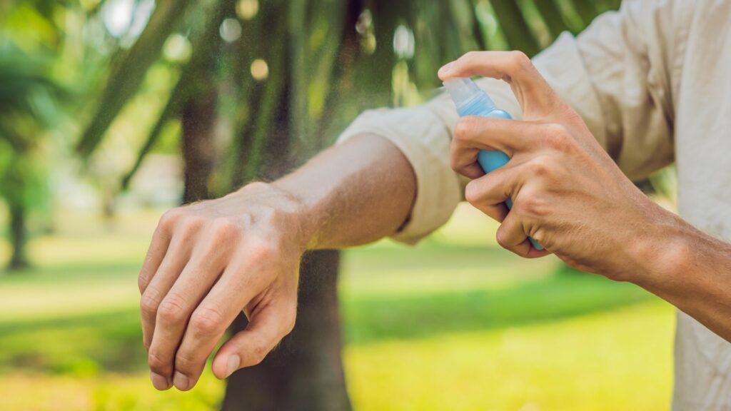 Spraying mosquito repellent.