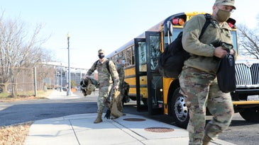 National Guard soldiers get off bus